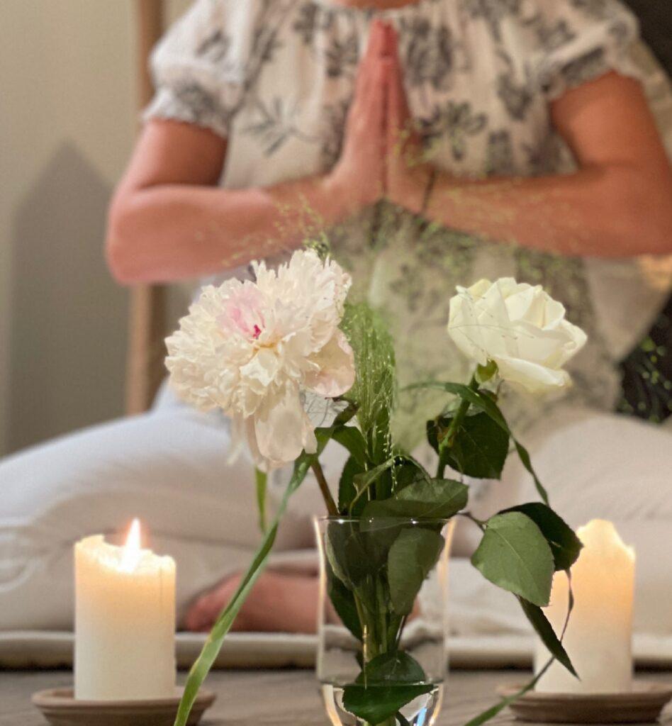 Två tända ljus och blommor framför en yogande kvinna